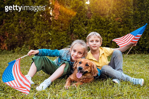 USA Memorial or Independence day concept with girl and boy holding American flags