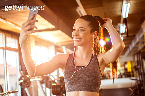 Smiling fitness girl with earphones using smartphone to take a selfie in the gym