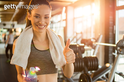 Fitness woman with bottle of water showing thumbs up in the gym