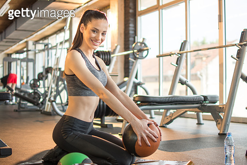 Beautiful sporty girl with exercise ball relaxing on mat at gym