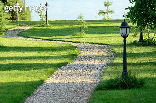 Path to lake on sunny summer day across green lawn