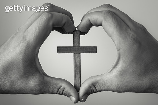 Hand holding wooden cross in heart shaped hand.