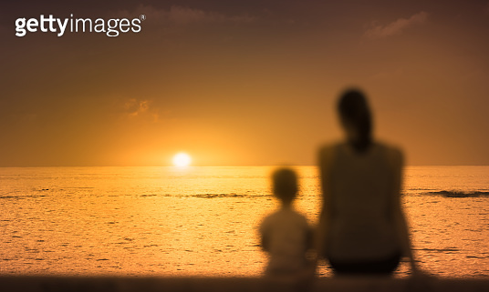 Mother and her son watching a beautiful sunset.