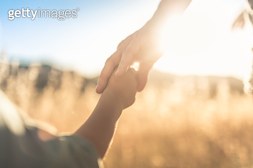 Child holding mothers hand walking outdoors.