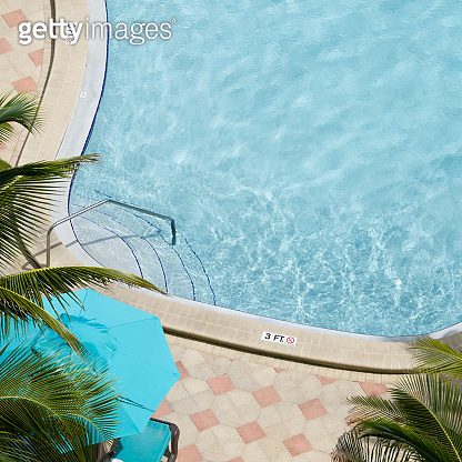 Aerial view of swimming pool with umbrella and sun lounger outdoors. Beautiful pool with clear water as texture background concept. Top view.