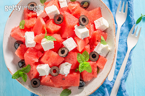 Top view of sweet watermelon salad with olives and feta