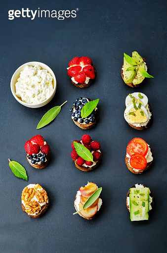 Ricotta and crostini appetizers with fillings on a black background