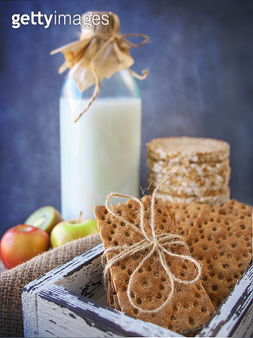 Healthy food. Three types of diet bread. Aerial buckwheat bread, wheat crisp bread and sunflower bread in a vintage box, against the background of milk and fruit.