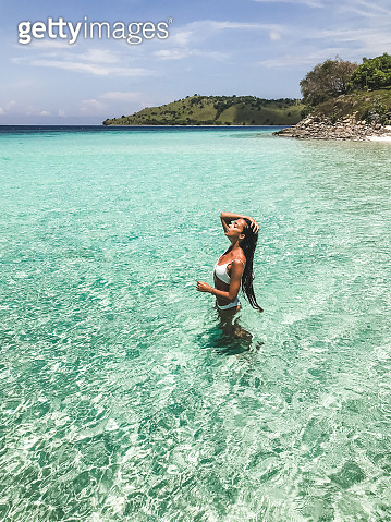 Slim tanned woman enjoying on in transparent turquoise ocean water on beach. Travel and vacations concept. Tropical background with empty space.
