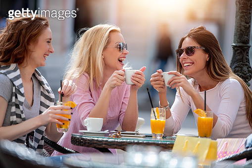 Smiling friends enjoying in cafe