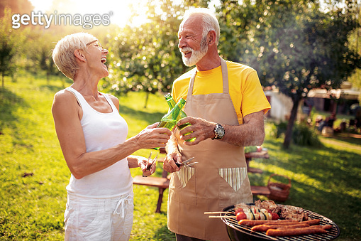 Senior couple making barbecue together