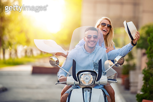 Couple in love riding a scooter,they are enjoying themselves on trip