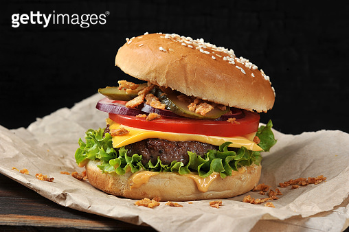 Cheeseburger on craft paper. Dried onions are scattered around the cheeseburger.