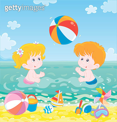 Children playing a colorful ball on a beach