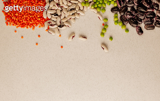 A set of different dried legumes is in glass cups and is a little scattered: red lentils, green peas, red beans, white beans. Legumes at the top of the frame and copy space.