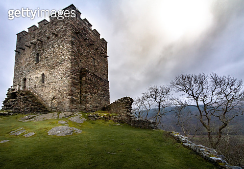 Magnificent moody sunset view of the tower of the crumbling ruins of Dolwyddelan in Snowdonia National Park