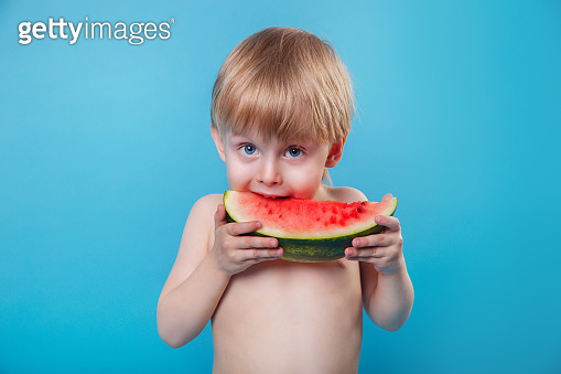 Funny little child eating watermelon on blue background