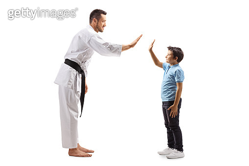 Man in karate kimono gesturing high-five with a boy