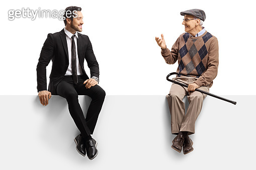 Buinessman and a senior man sitting on a panel and having a conversation