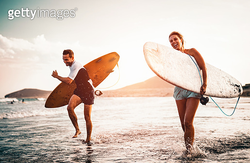 Happy surfer couple running with surfboards along the sea shore - Sporty people having fun going to surf together at sunset - Extreme surfing sport and youth relationship lifestyle concept