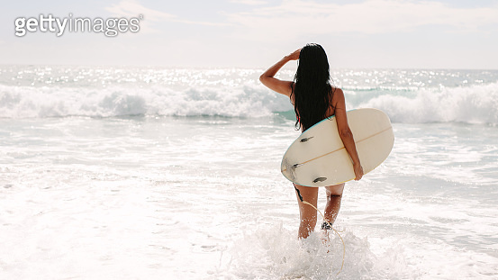 Female surfer going on surf in the sea