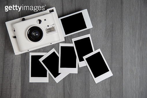 Vintage white instant camera with isolated blank photographs