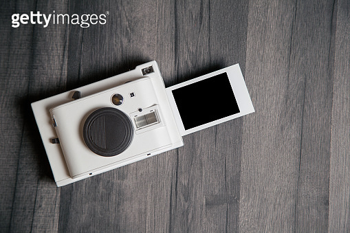 Vintage white instant camera with isolated blank photograph