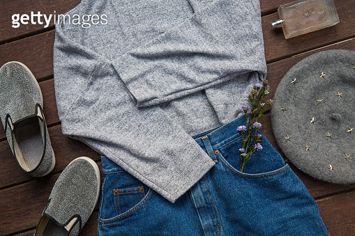 Spring female outfit. Set of clothes, shoes and accessories on wooden background. Fashion concept