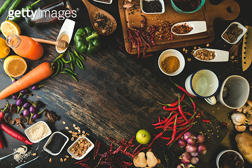 Spices for use as cooking ingredients on a wooden background with Fresh organic vegetables on wood. Healthy food herbs and spices. Organic vegetables on rustic wood.