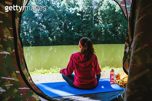 Young woman in the sport wear outfit is sitting and relaxing in the camping in the forest.