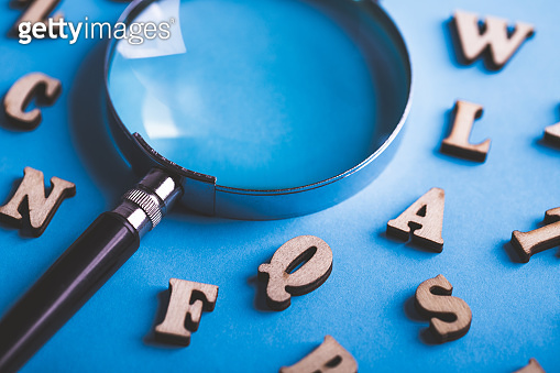 Magnifying With Wooden Alphabets Around On Blue Background