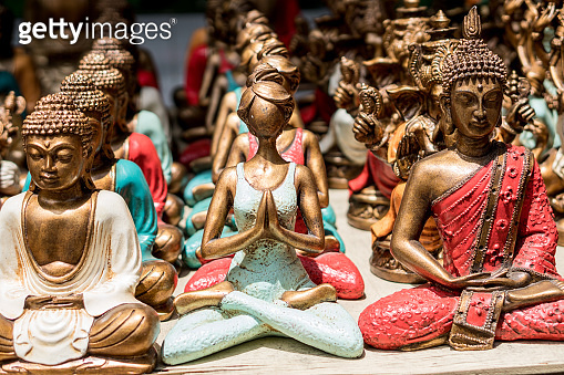 Statue of a yoga posing girl and a buddha sold as a souvenir on a market