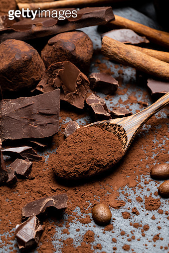 Dark or milk organic chocolate pieces and cocoa powder on dark concrete backgound