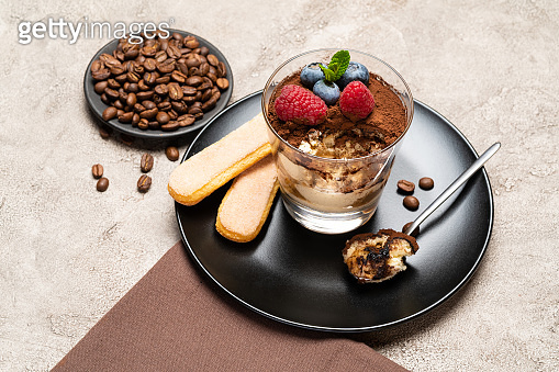 Classic tiramisu dessert portion with blueberries and raspberries in a glass cup on concrete background