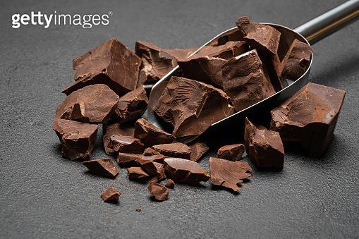Dark Chocolate chunks in metal scoop on dark concrete background