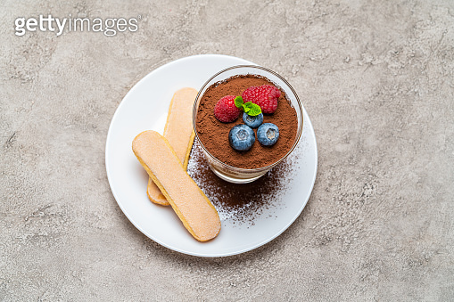 Classic tiramisu dessert with blueberries and raspberries and savoiardi cookies in a glass on concrete background