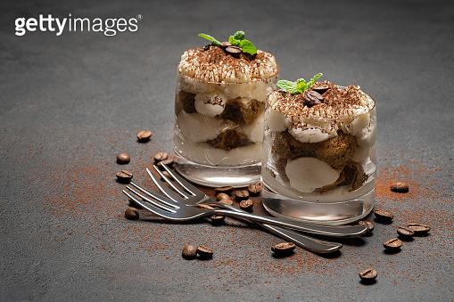 two portions Classic tiramisu dessert in a glass on dark concrete background