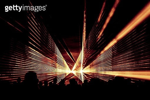 Orange laser show nightlife club stage with party people crowd