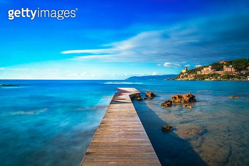 Castiglioncello bay wooden pier, rocks and sea. Tuscany, Italy.