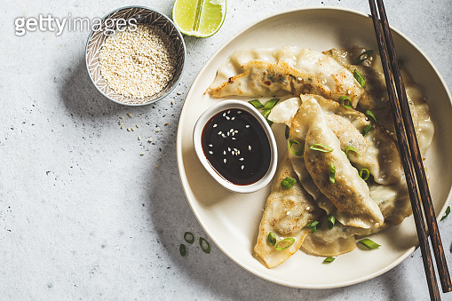 Fried Korean dumplings with green onion and sauce on white plate, top view.