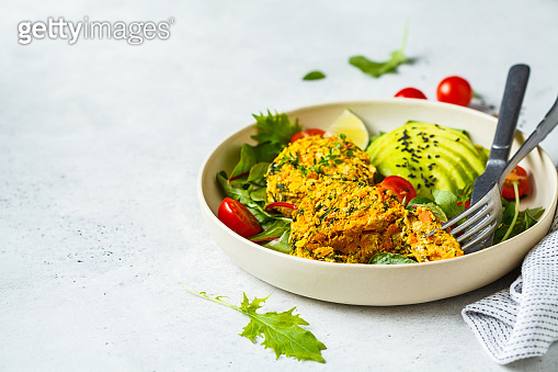 Vegan pumpkin and quinoa cutlets with salad in a white plate.