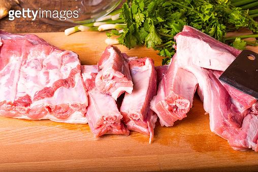 Raw chopped pork ribs on a wooden cutting board