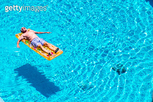 Senior aged man sleep and relax enjoying the blue water of swimming pool lay down on red watermelon lilo - summer vibes and retired lifestyle for caucasian people