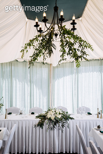 Wedding restaurant interior table, no people. White table set decorated with green leaves and white peonies.