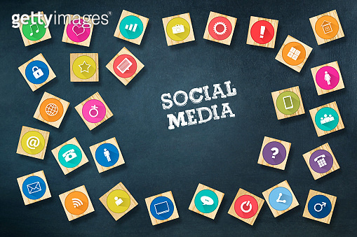 Social media concept with social icons on wooden blocks. Dark blue background.