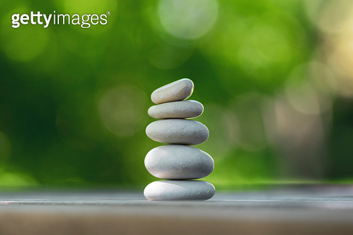 Harmony and balance, cairns, simple poise pebbles on wooden table, natural green background, simplicity rock zen sculpture