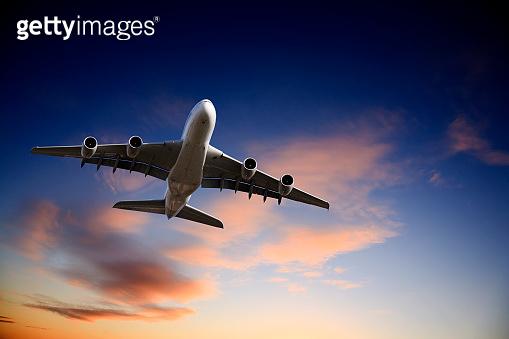 Jet Airplane Landing from Bright Twilight Sky