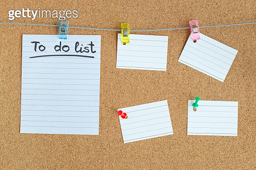 Cork memory board with blank peaces of paper hanging on rope with clothes pin and pinned on board, horizontal