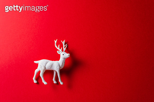White reindeer toy on red background.