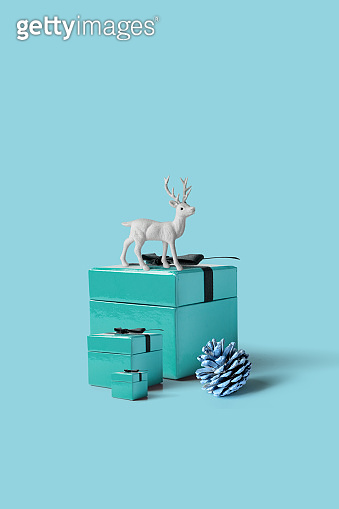Christmas gift box with a white reindeer on pastel blue background, minimal composition